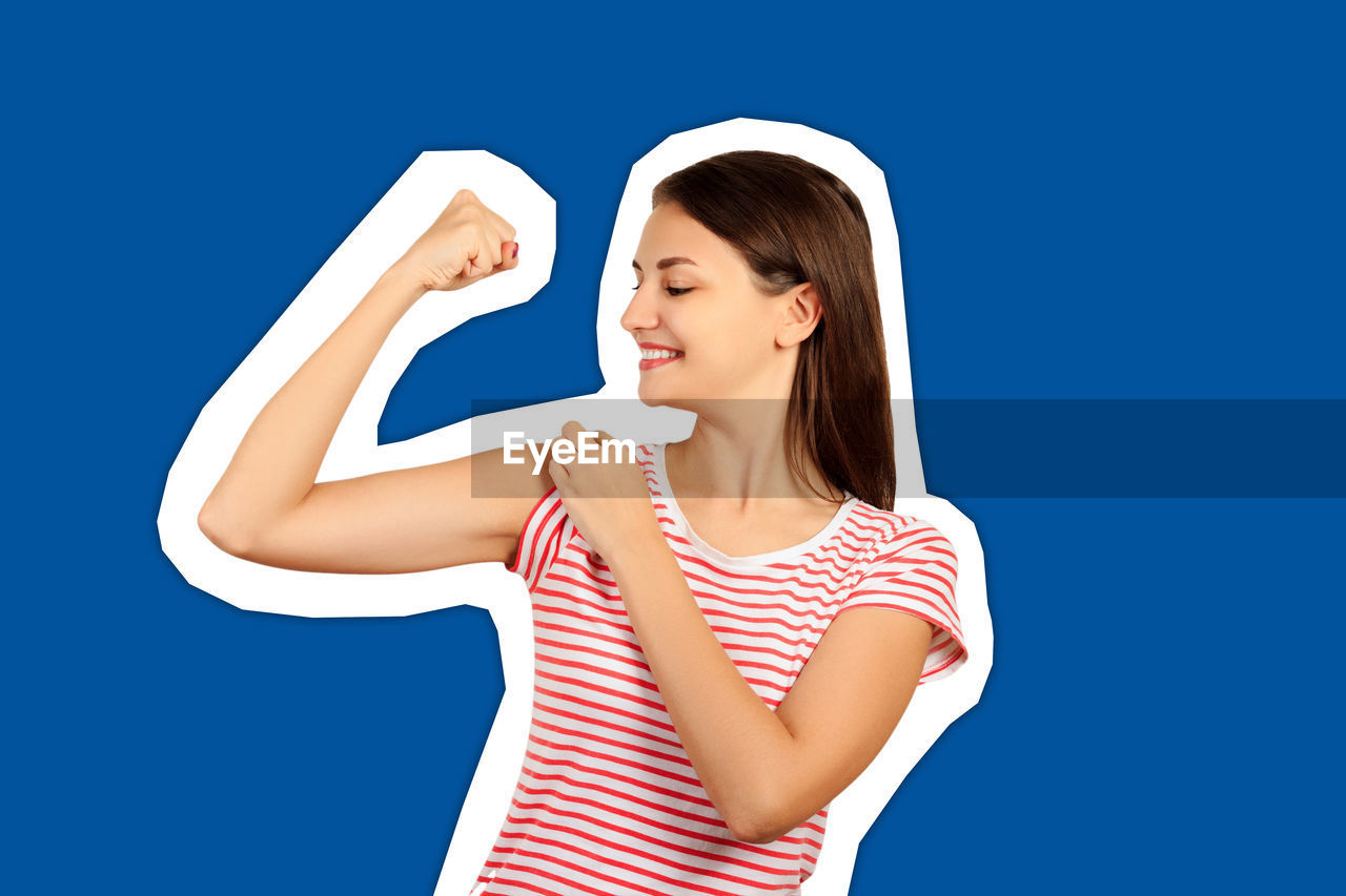 Smiling young woman flexing muscles against blue background
