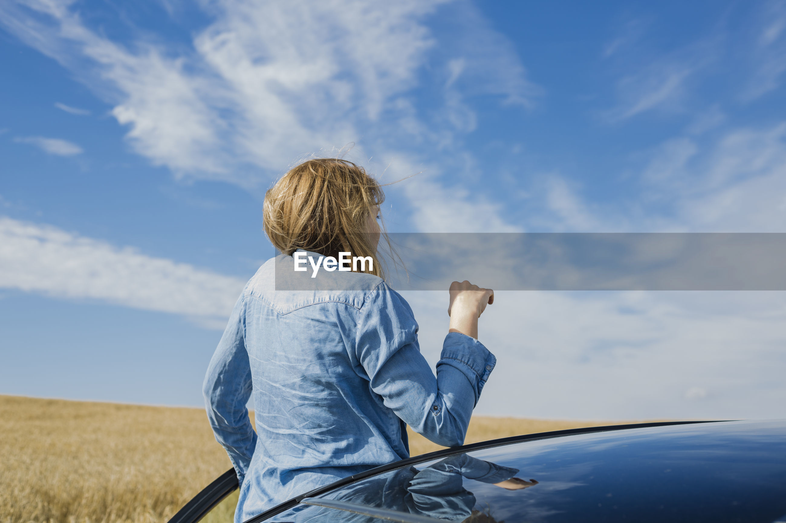 Woman peeking from car against sky