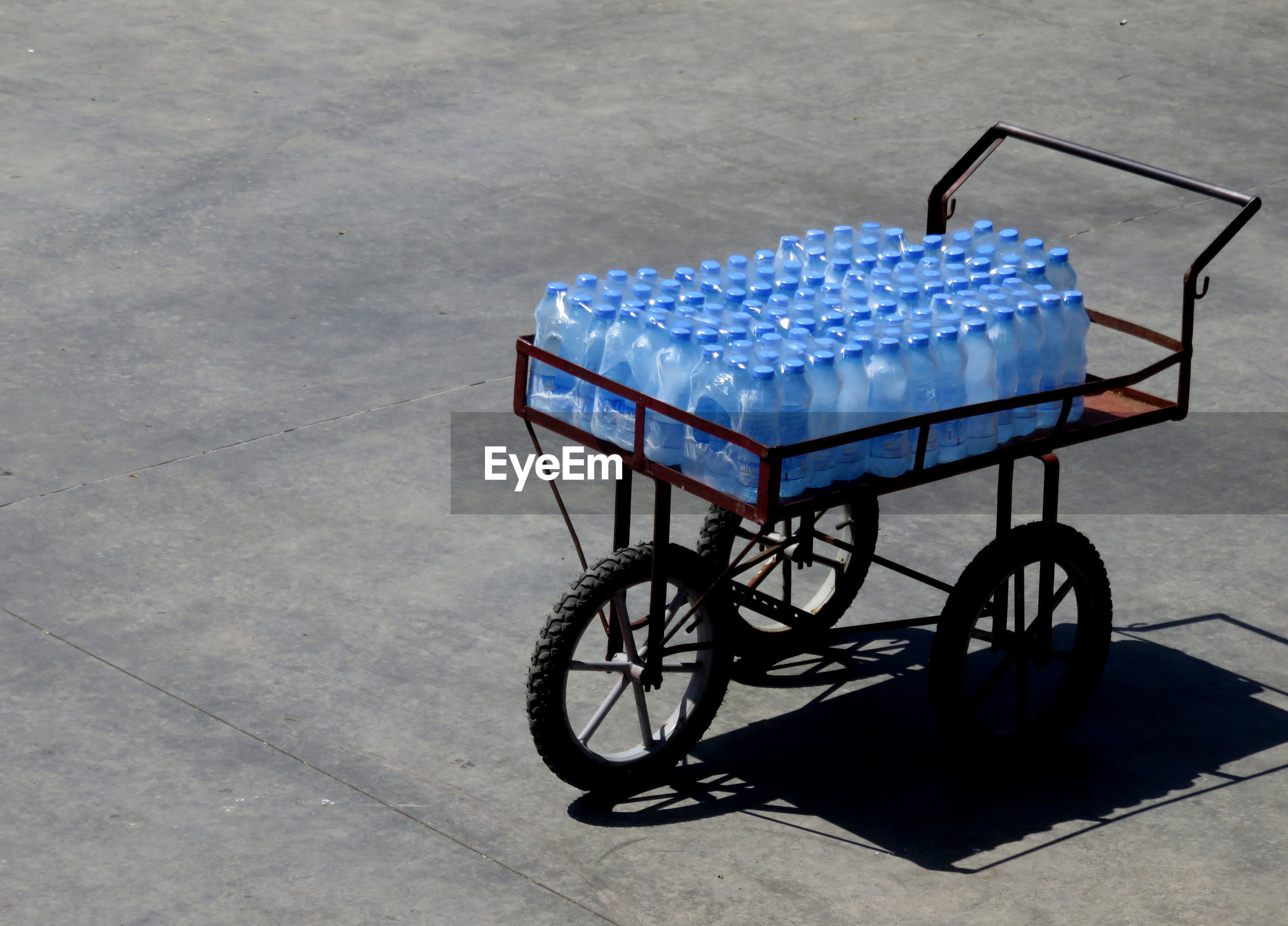 High angle view of bicycle with basket of water bottles