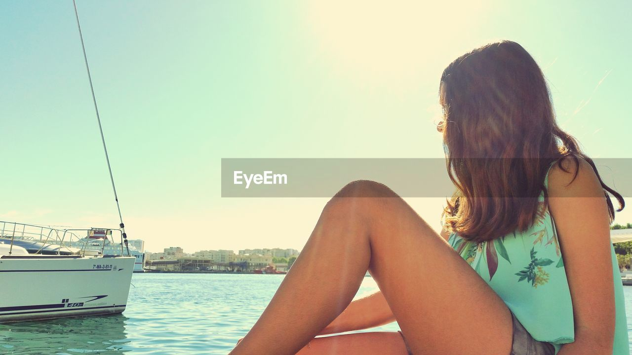 Young woman sitting while looking at motorboat against clear sky