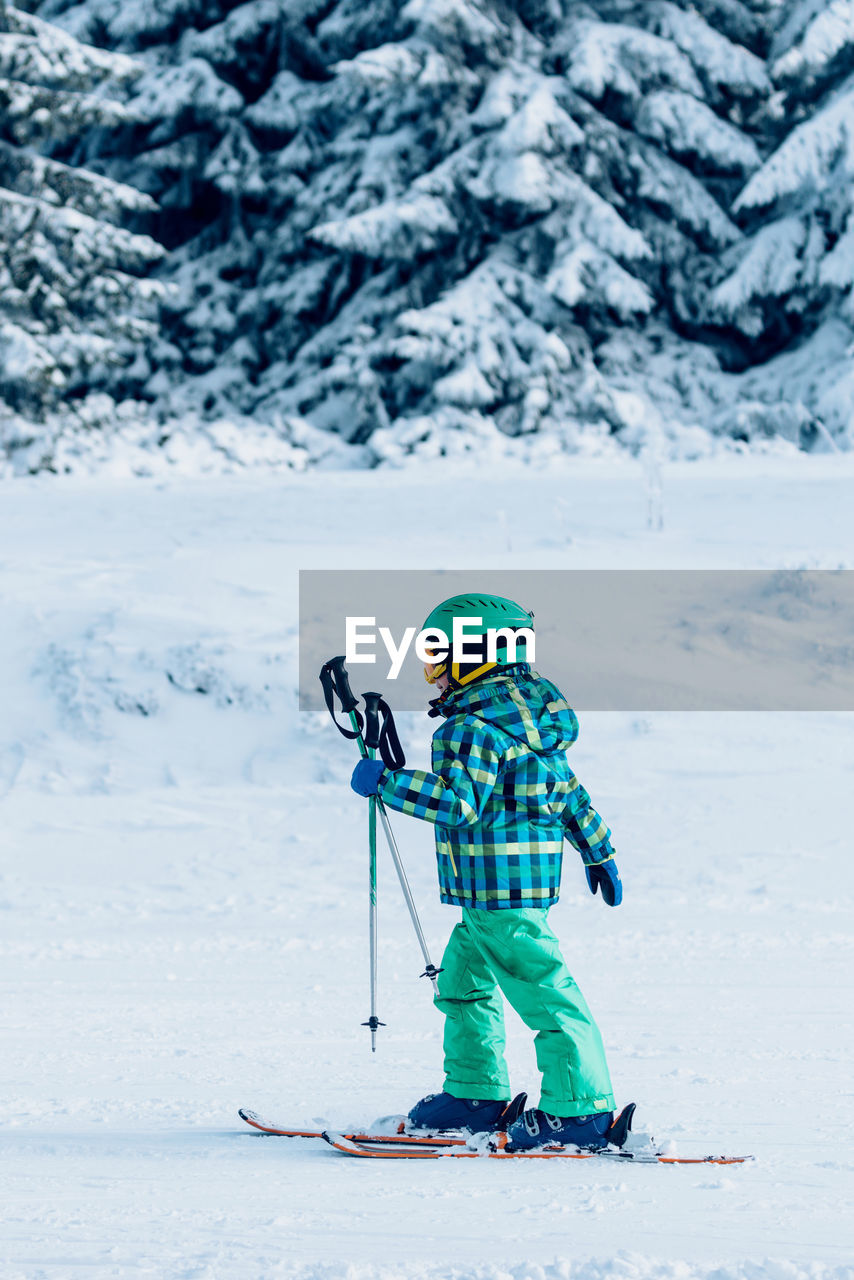 Full length of boy skiing against snow covered trees