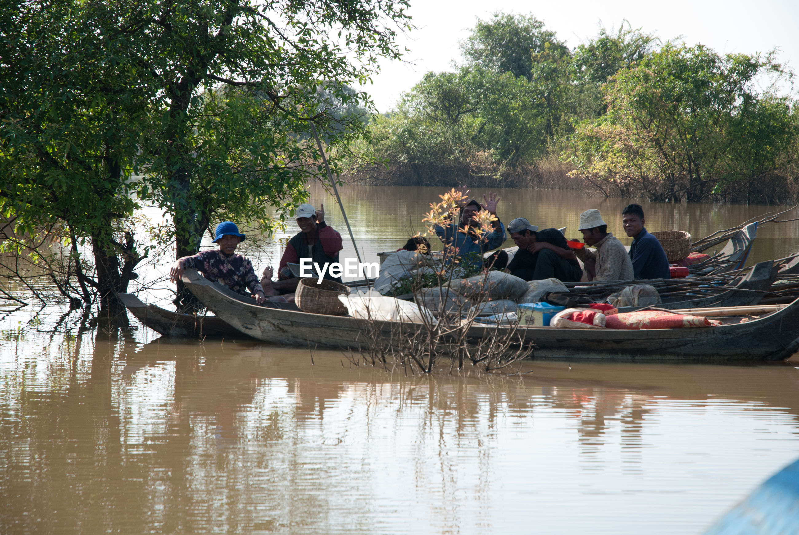PEOPLE SITTING ON BOAT IN RIVER