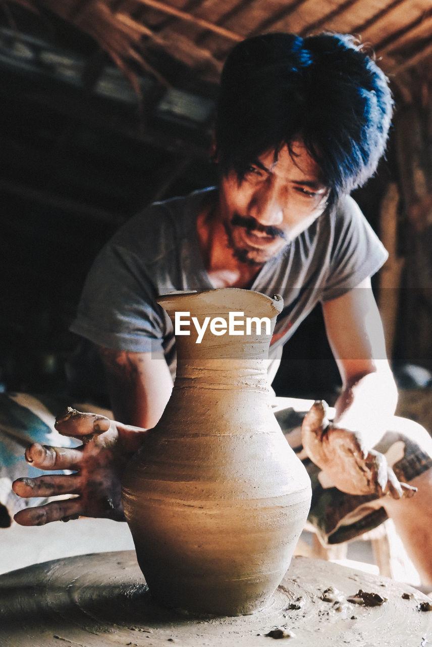 Man making pot on pottery wheel