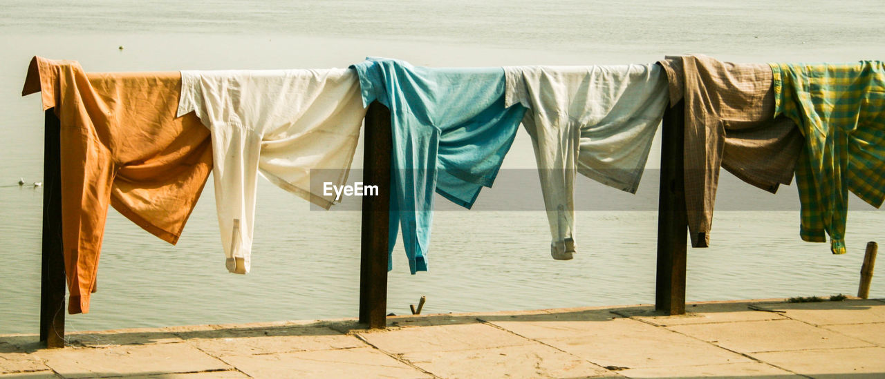 Clothes drying on pier against river