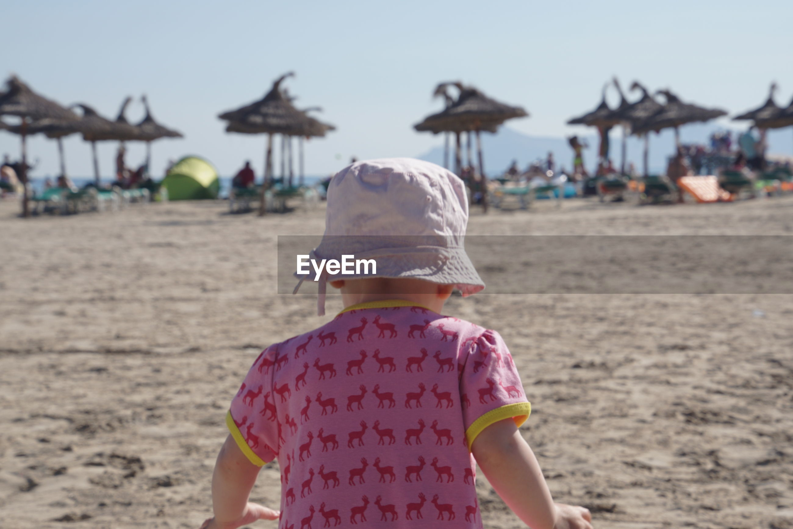 Rear view of girl at beach against sky