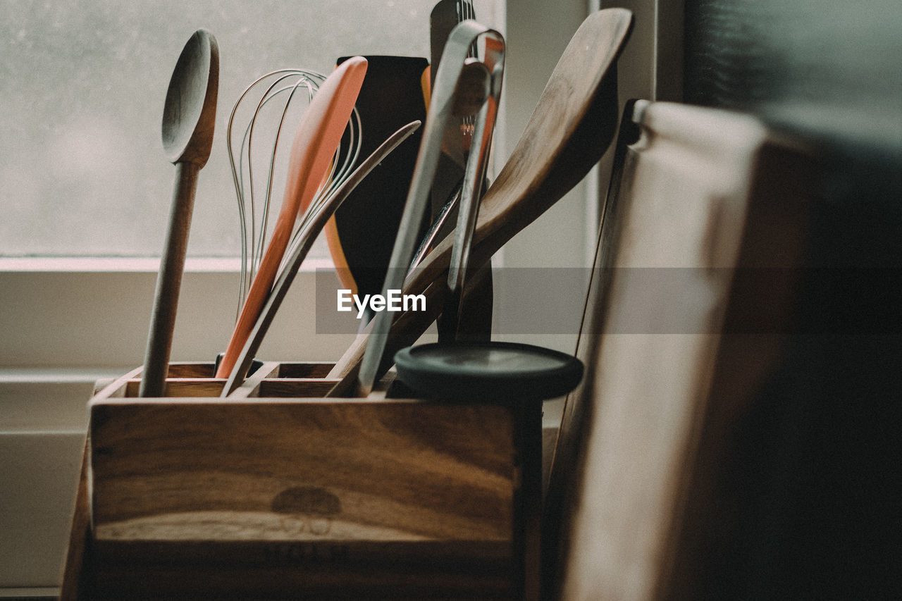 Close-up of kitchen utensils in wooden container at home