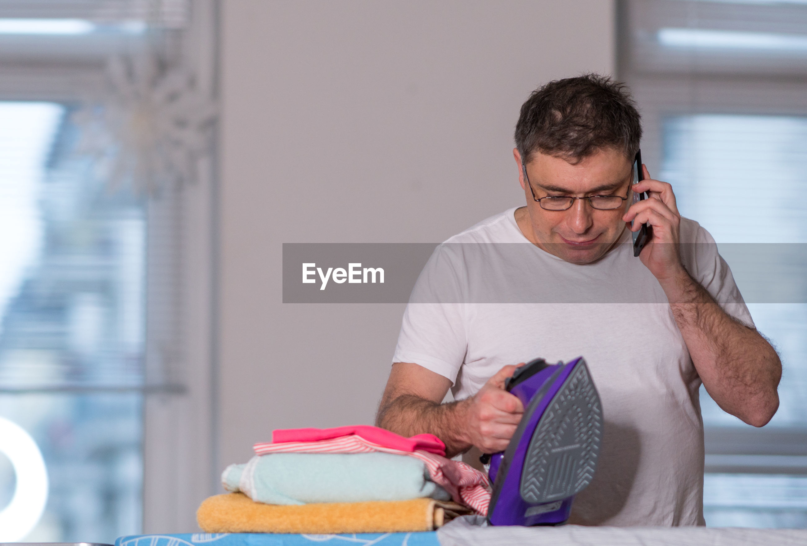 Man talking on phone while holding iron at home