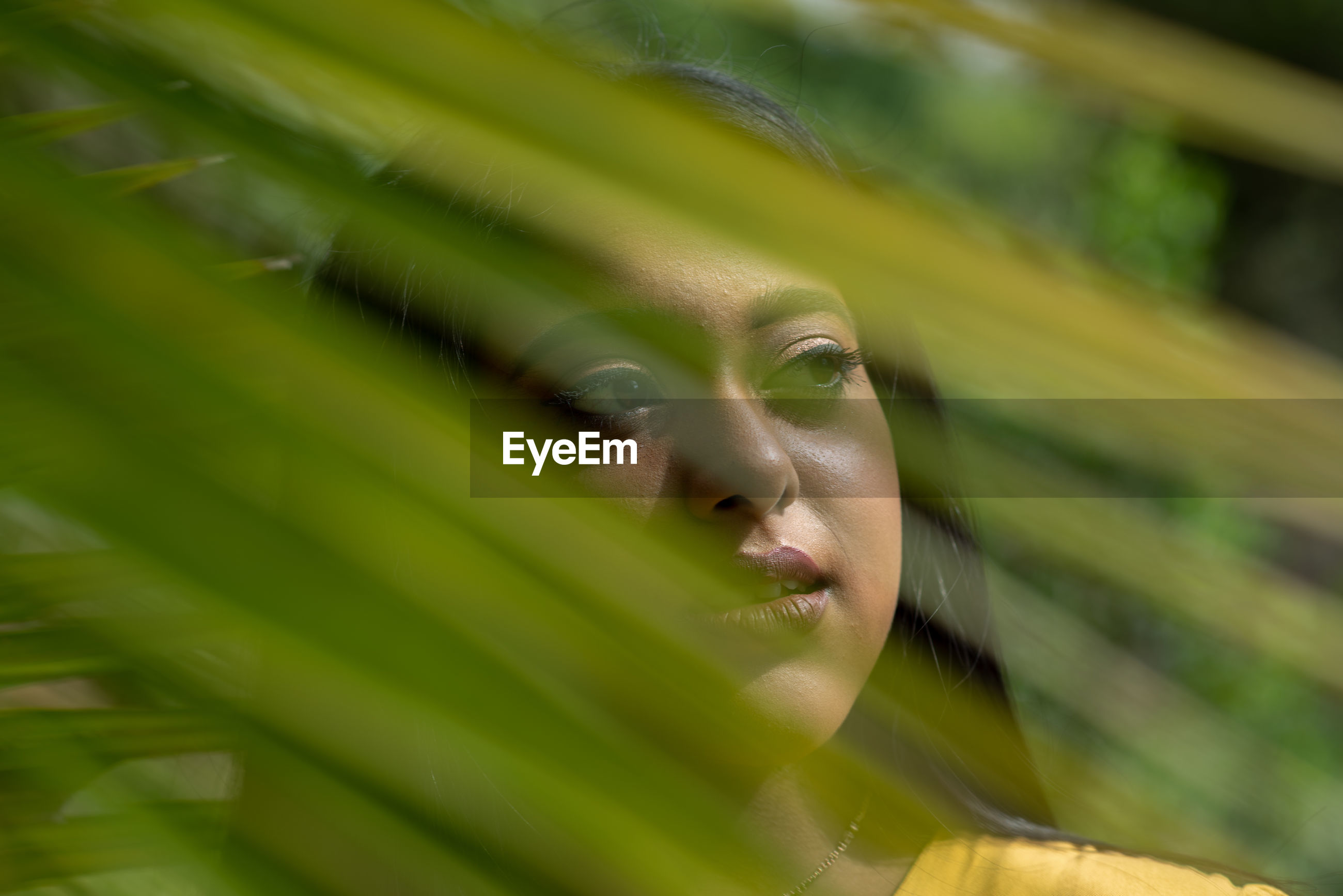 Close-up of young woman looking away seen through green leaves