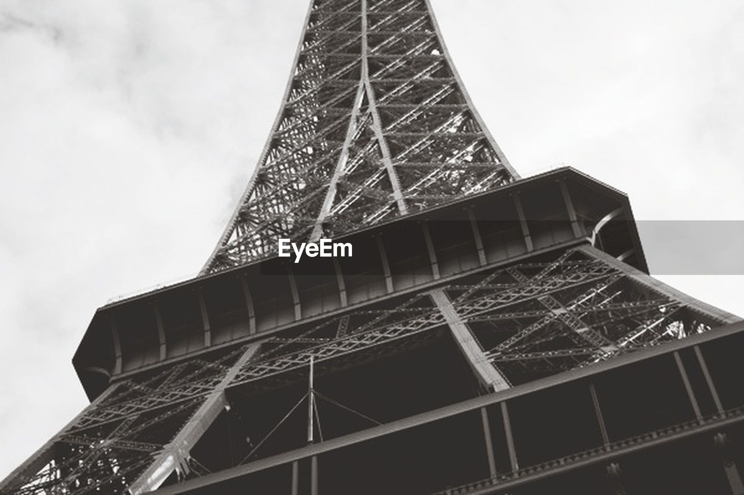 low angle view, architecture, built structure, tall - high, tower, sky, building exterior, famous place, international landmark, capital cities, travel destinations, modern, skyscraper, tourism, city, architectural feature, eiffel tower, metal, travel, tall