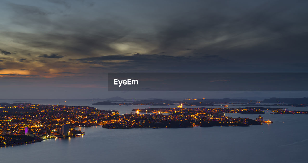 Aerial View Of Illuminated Cityscape By Sea Against Sky During Sunset
