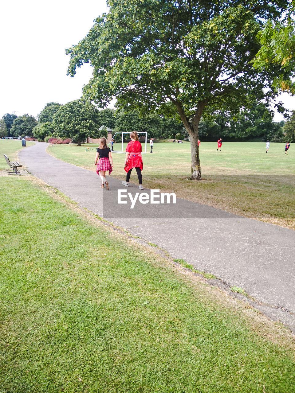 Rear view of friends walking on footpath in park