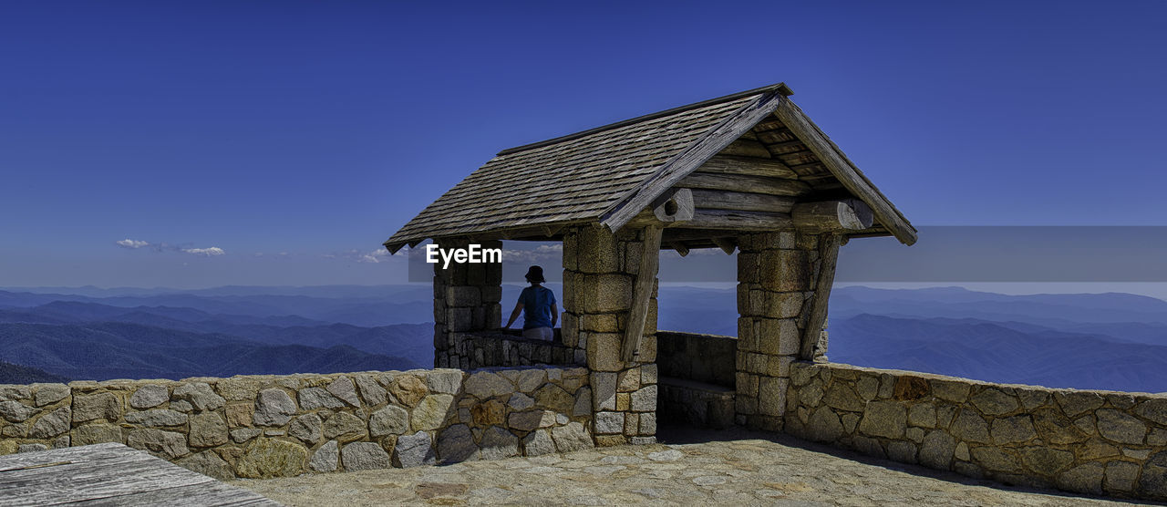 Rear View Of Woman Looking At Mountains While Standing At Observation Point