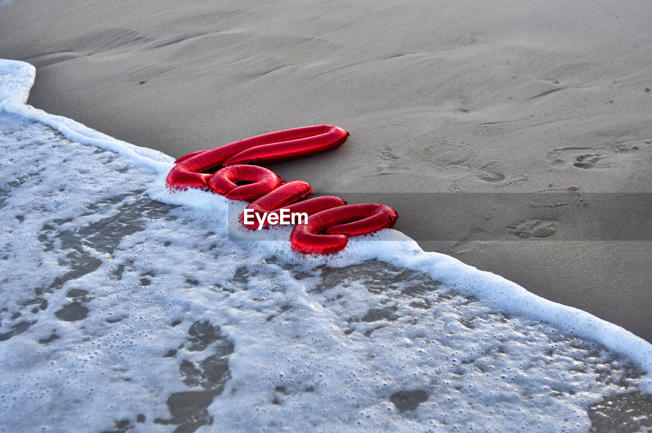 red, land, sand, beach, high angle view, nature, day, no people, love, beauty in nature, heart shape, positive emotion, outdoors, water, winter, sport, emotion, snow, warm clothing, personal accessory