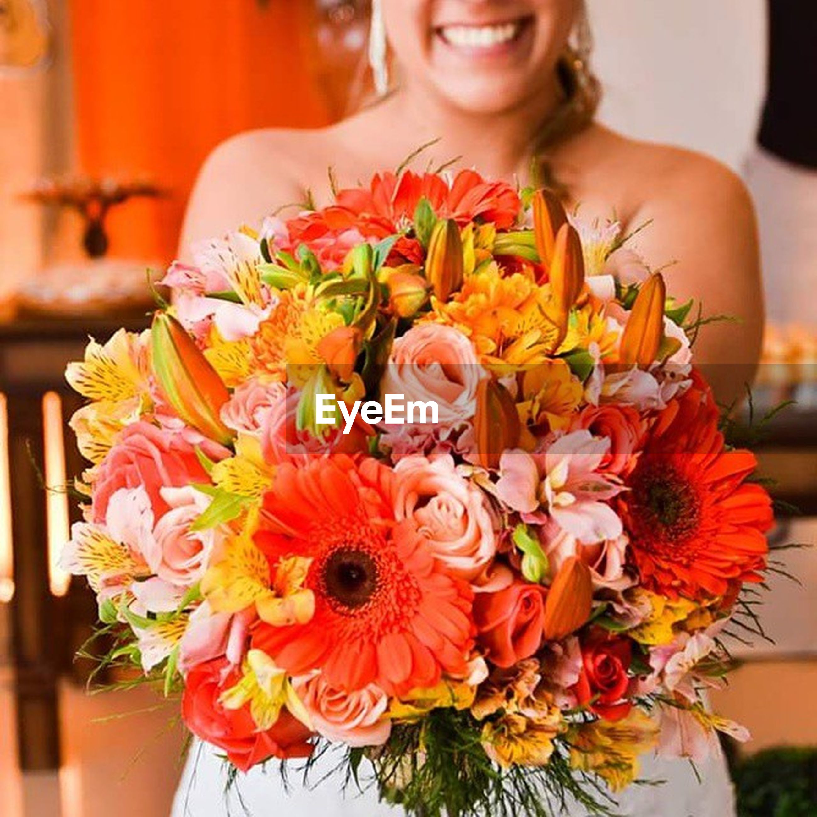 flower, freshness, indoors, lifestyles, person, focus on foreground, holding, front view, leisure activity, fragility, bouquet, young women, casual clothing, young adult, petal, looking at camera, close-up, smiling