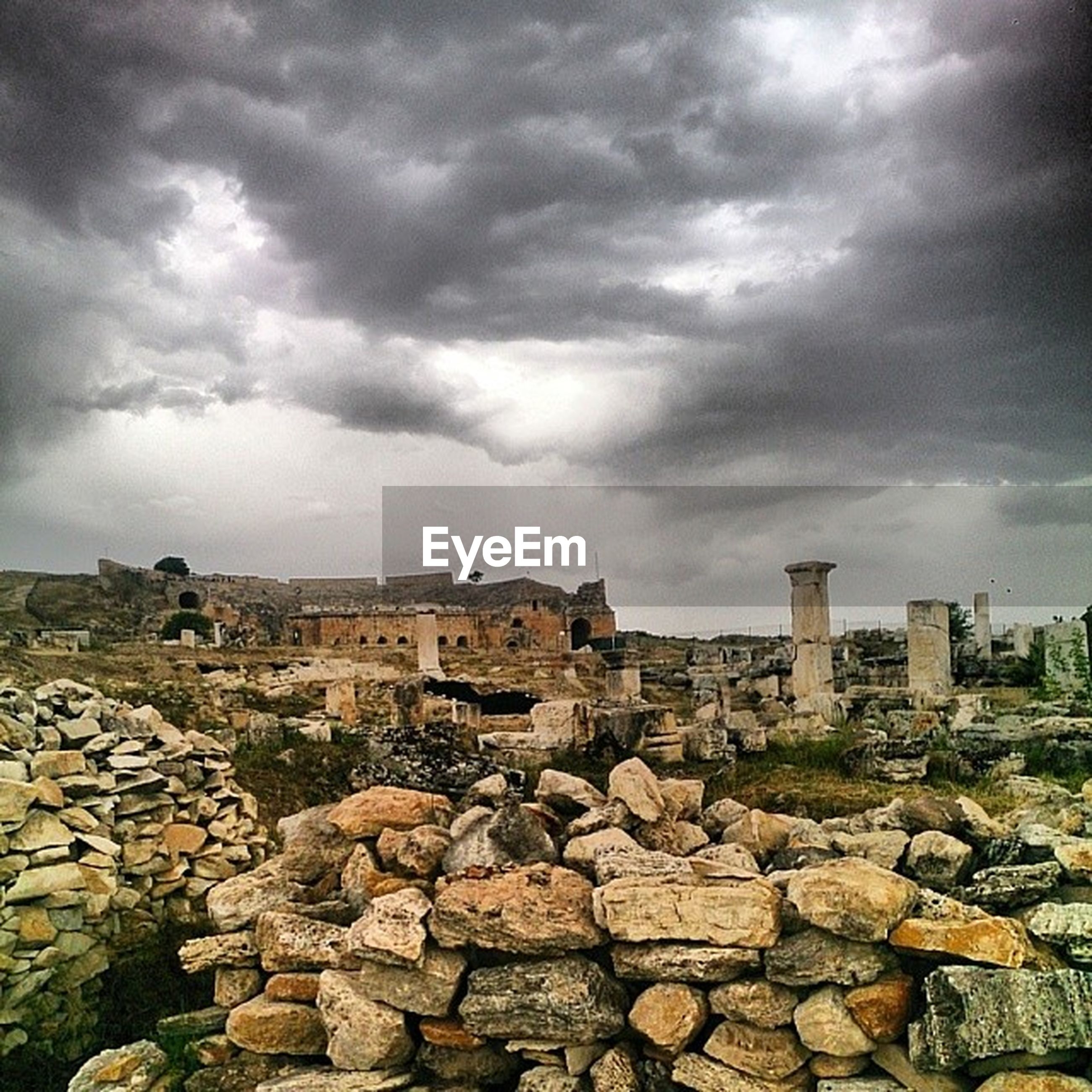 sky, cloud - sky, building exterior, architecture, built structure, cloudy, cloud, overcast, rock - object, stone wall, stone - object, weather, day, residential building, house, outdoors, residential structure, city, no people, stone