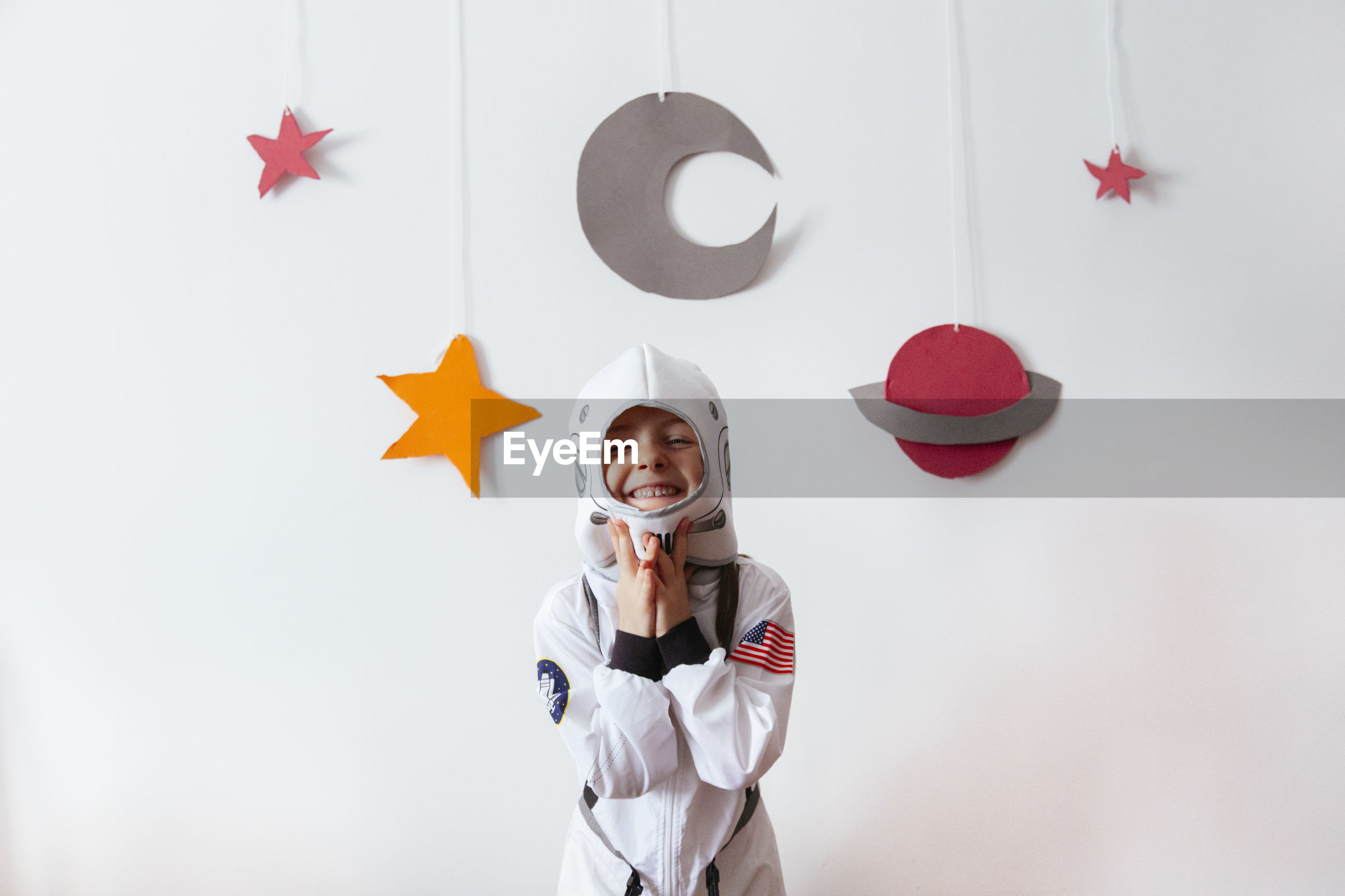 Portrait of smiling girl wearing space suit against wall at home