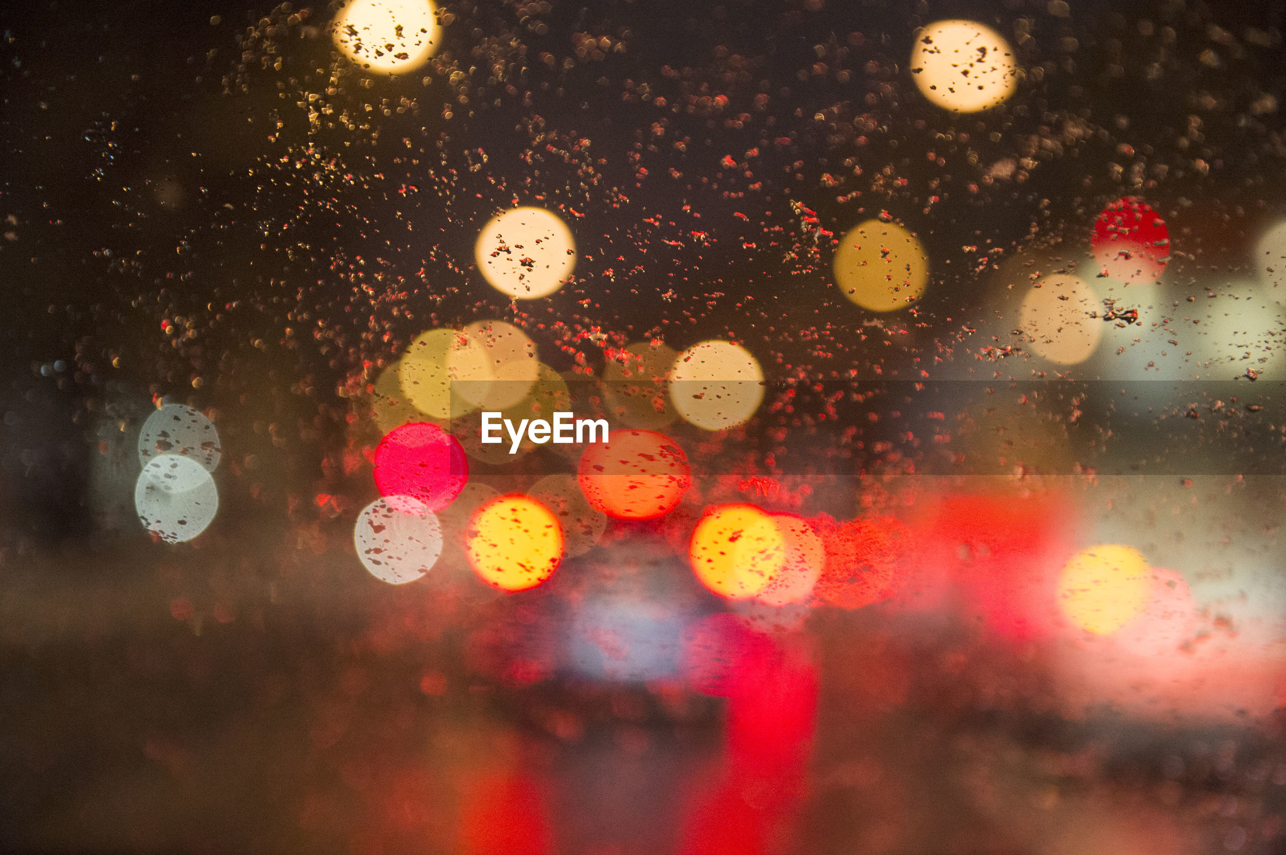 Close-up of lights seen through wet glass window in rainy season
