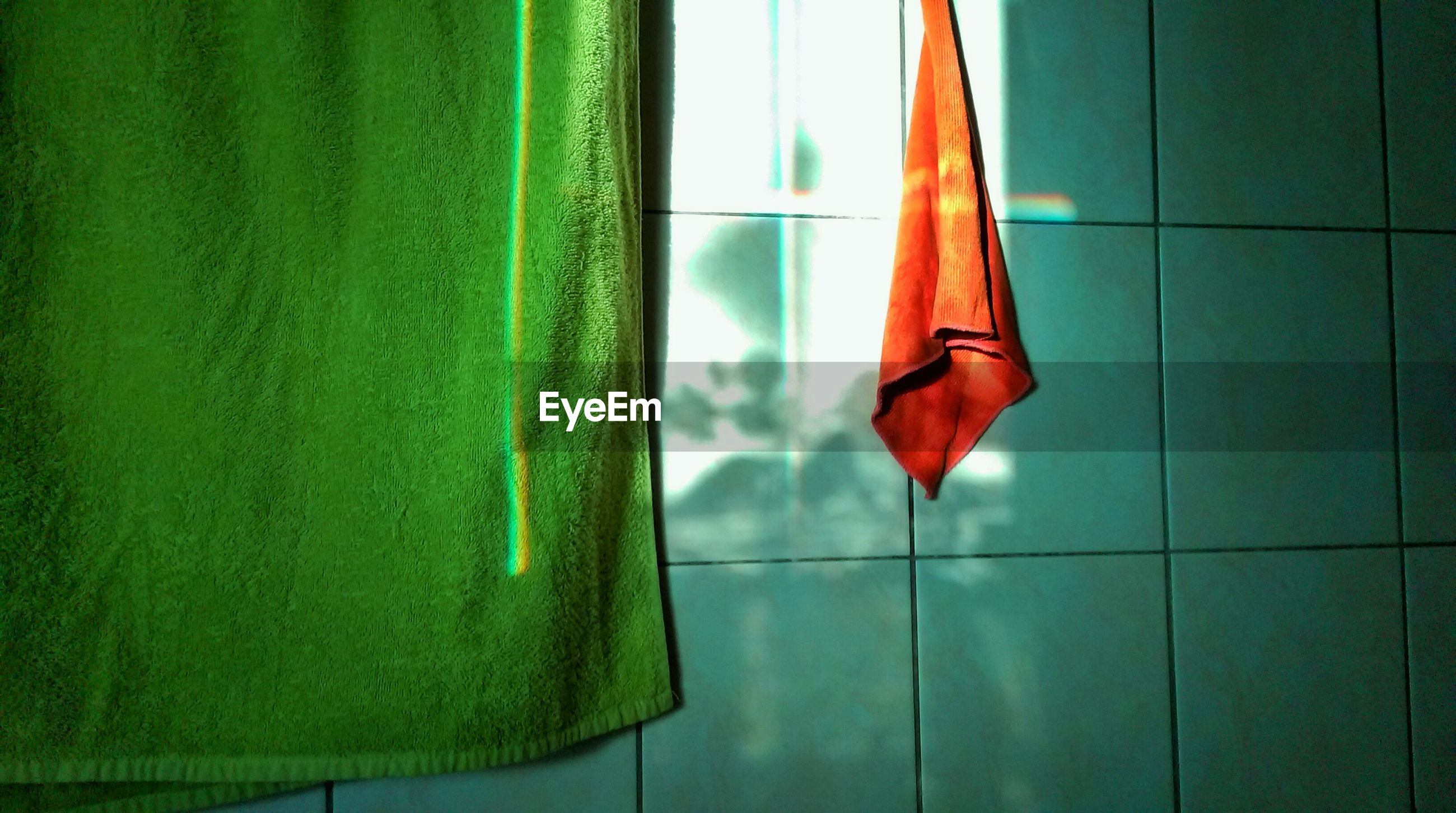 Close-up of towel against tiled wall