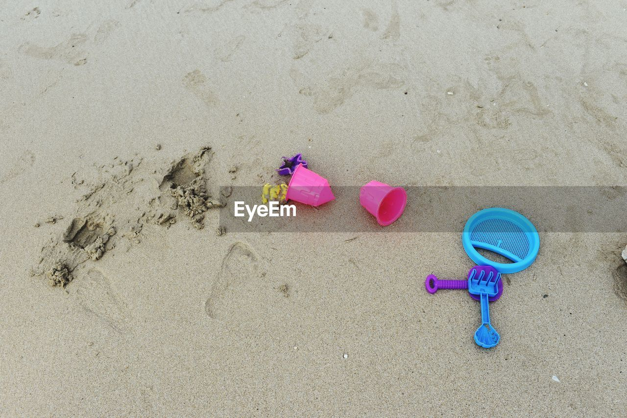 sand, beach, land, toy, pink color, nature, plastic, childhood, high angle view, day, sand pail and shovel, flower, absence, beauty in nature, outdoors, flowering plant, vacations, trip, animal representation