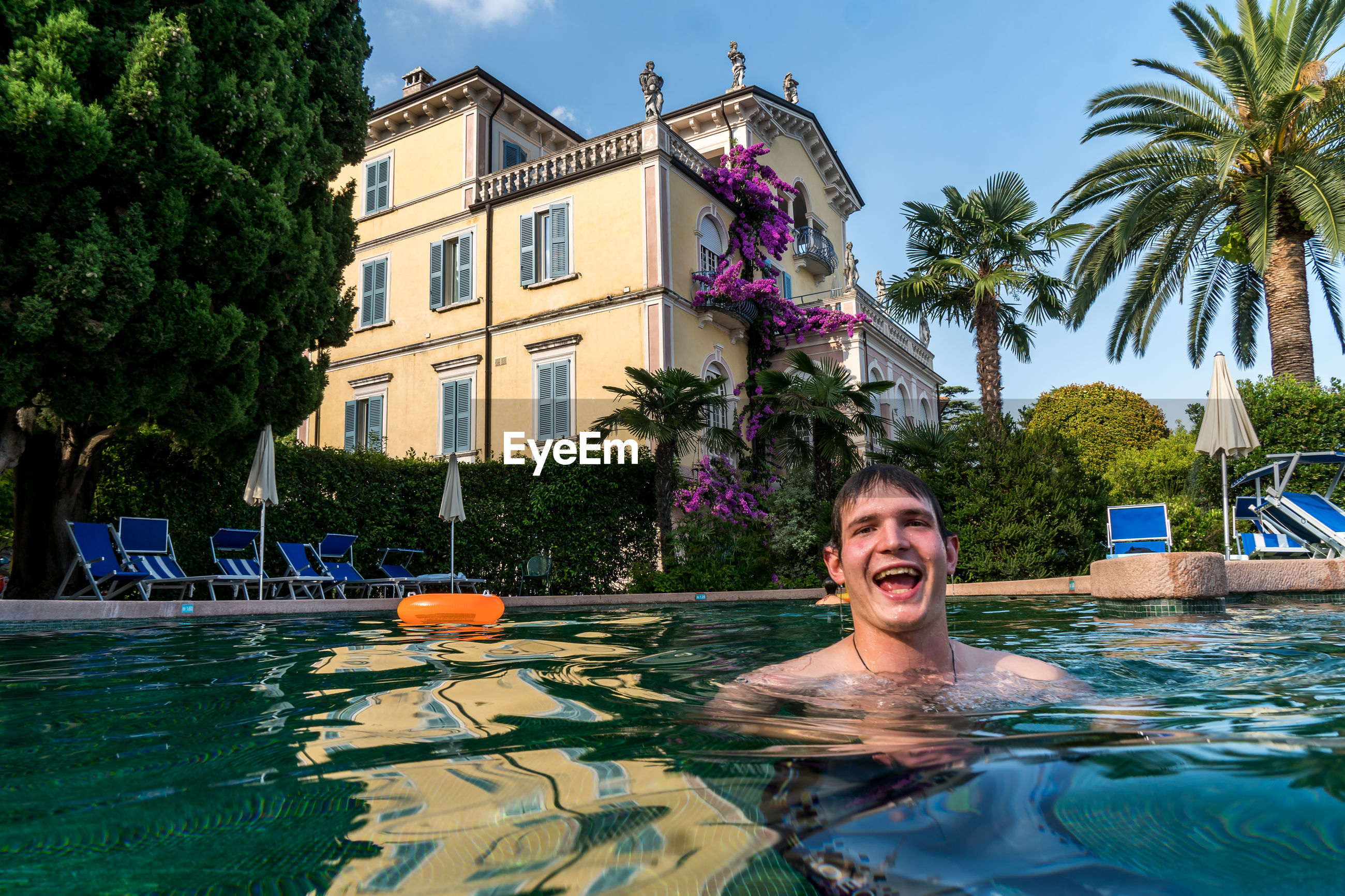 Portrait of smiling man swimming in pool against house
