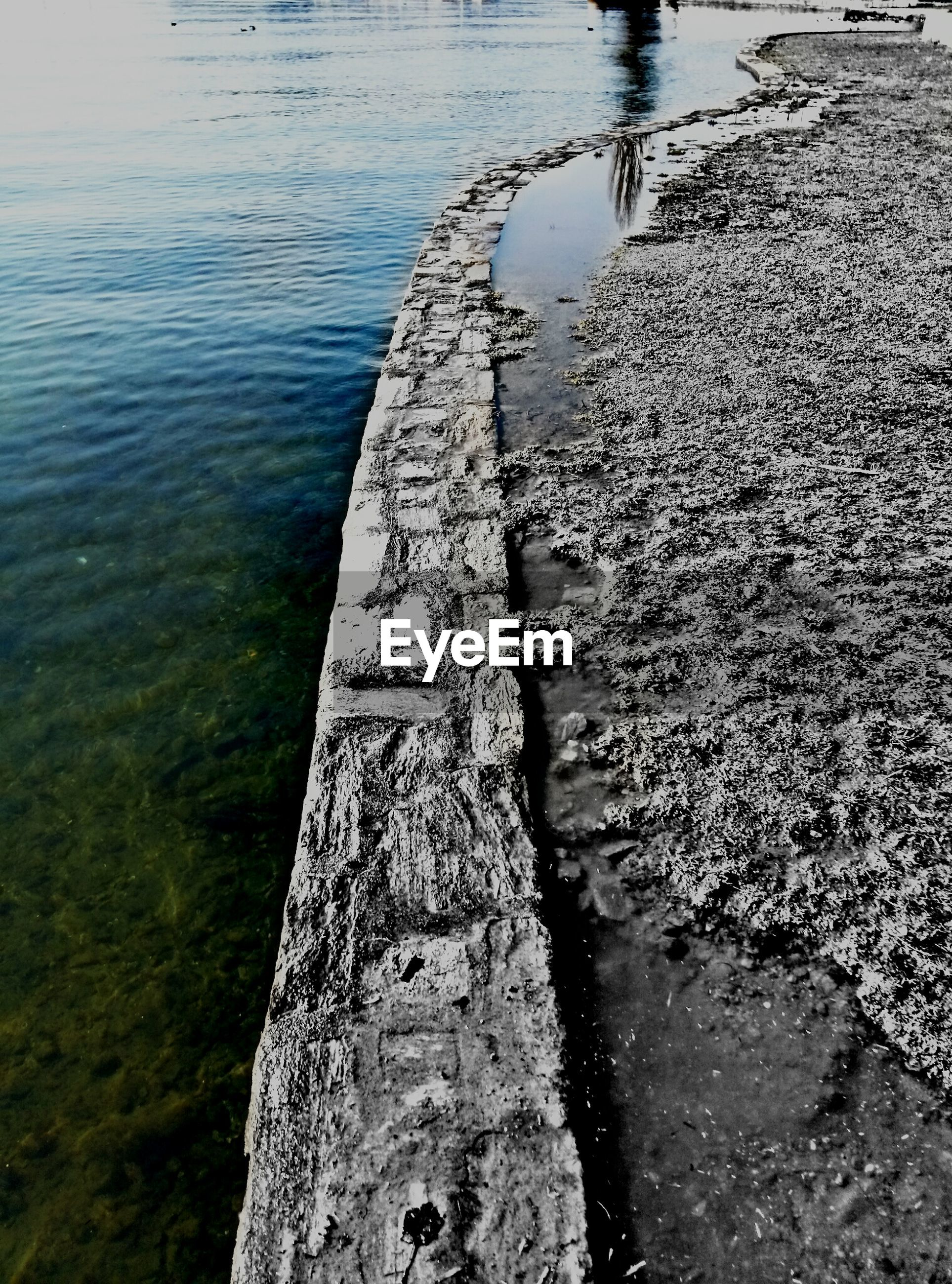 water, high angle view, sea, rippled, reflection, lake, nature, tranquility, rock - object, day, outdoors, textured, river, waterfront, no people, pier, weathered, stone - object, sunlight, beauty in nature
