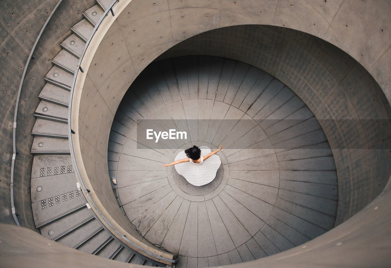 High Angle View Of Woman And Spiral Staircase
