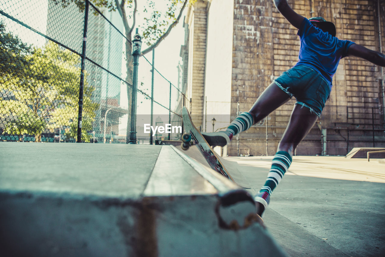 Rear view of young woman skateboarding at skateboard park