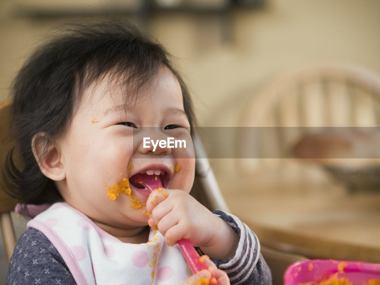 Close-up of cute baby girl eating mashed potatoes at home