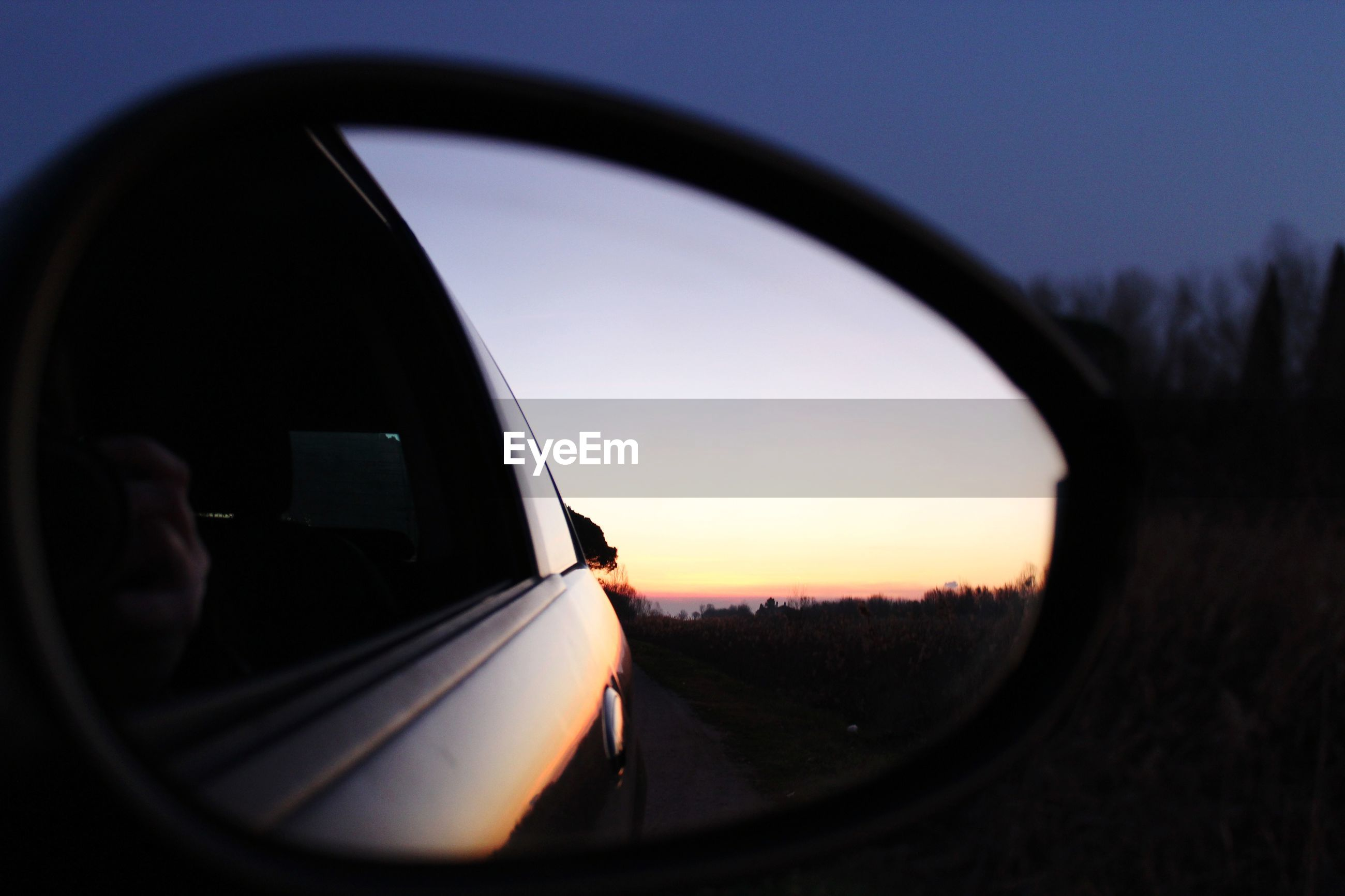 Reflection of sunset in car side-view mirror