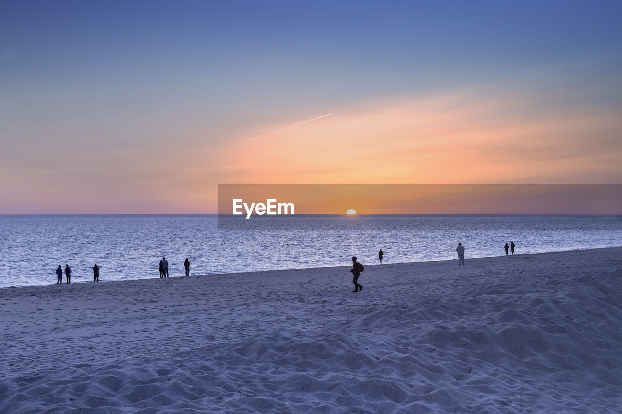 People at sandy beach during sunset