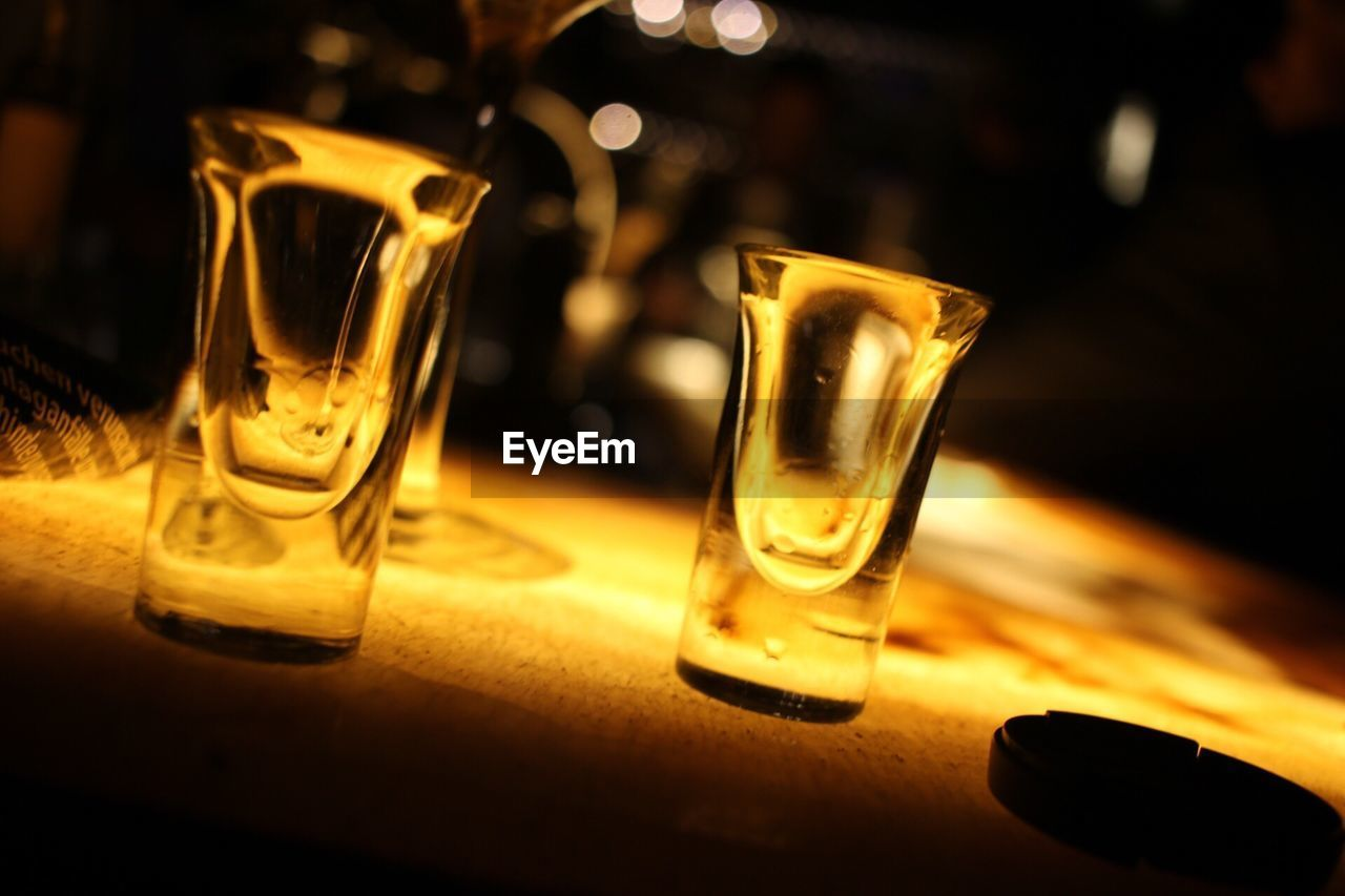 table, food and drink, refreshment, close-up, indoors, no people, drink, focus on foreground, drinking glass, alcohol, bar counter, freshness, shot glass, bar - drink establishment, yellow, night