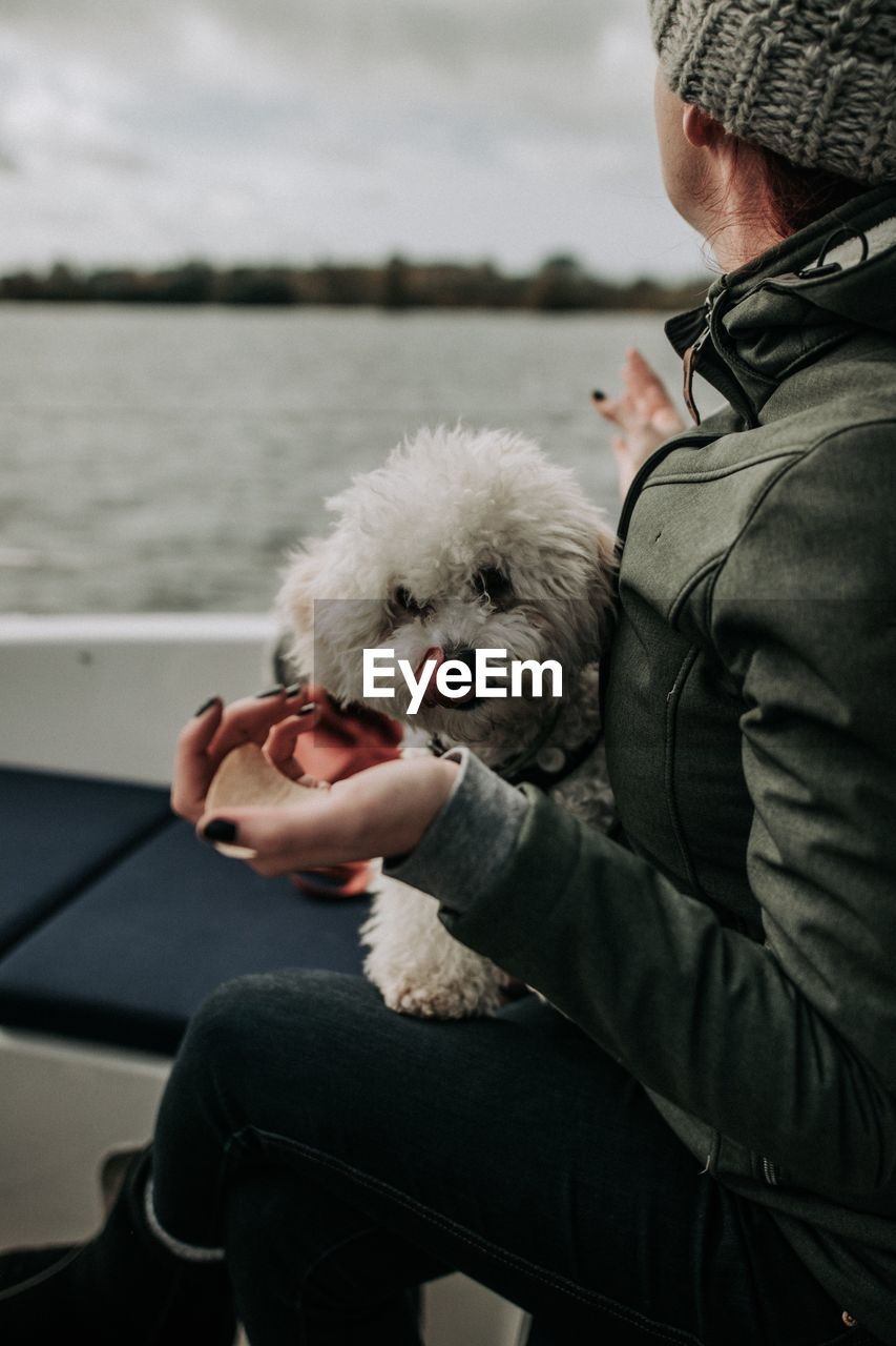 Woman with dog sitting in boat on sea against sky