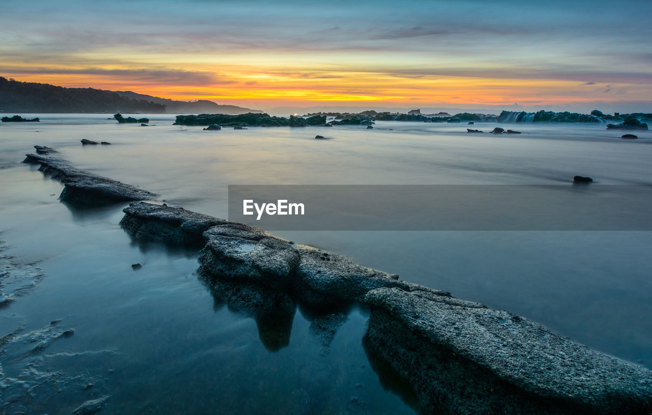 water, sky, sunset, scenics - nature, beauty in nature, tranquility, cloud - sky, tranquil scene, sea, waterfront, nature, orange color, no people, idyllic, non-urban scene, outdoors, reflection, remote, groyne