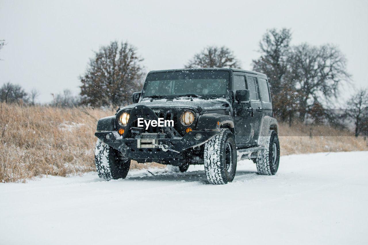 VINTAGE CAR ON SNOW FIELD
