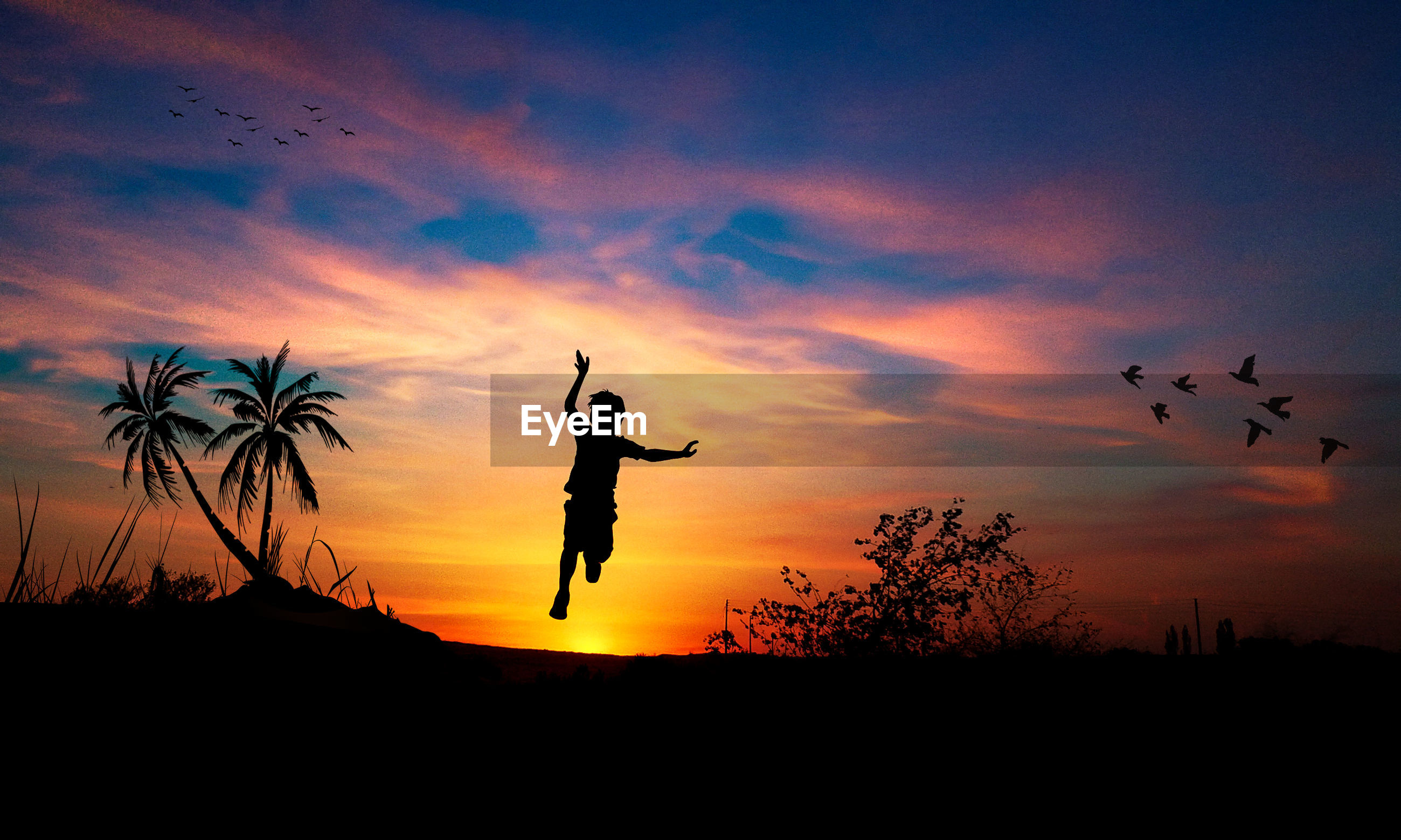 Silhouette boy jumping over field against romantic sky during sunset