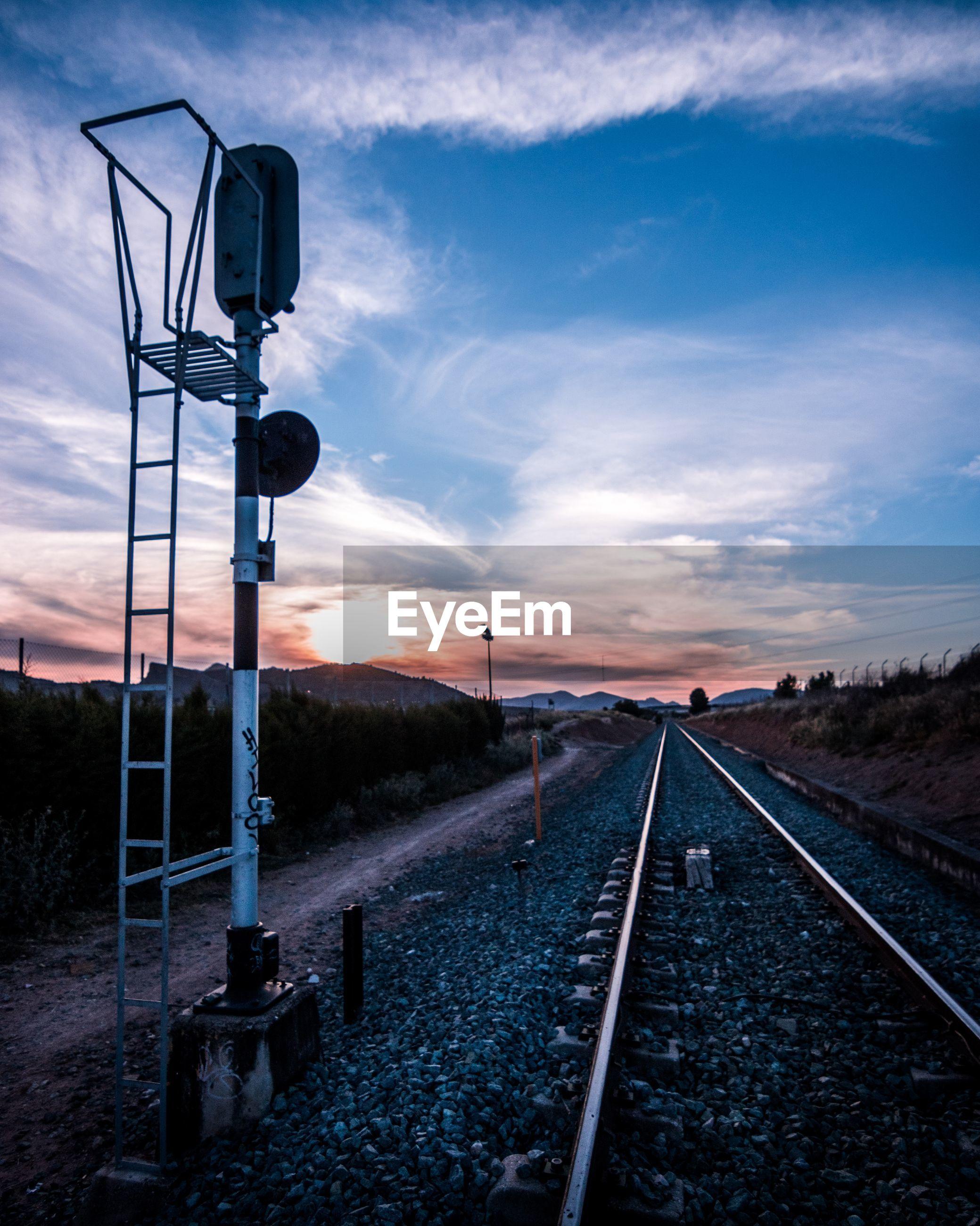 Railroad tracks by signal against sky