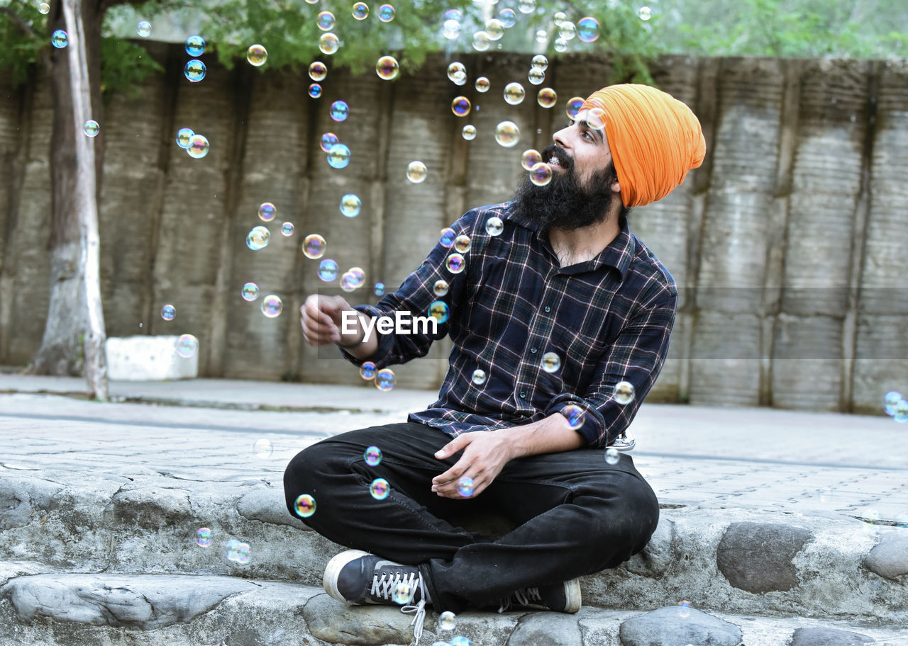 Full Length Of Man Wearing Turban Sitting By Bubbles