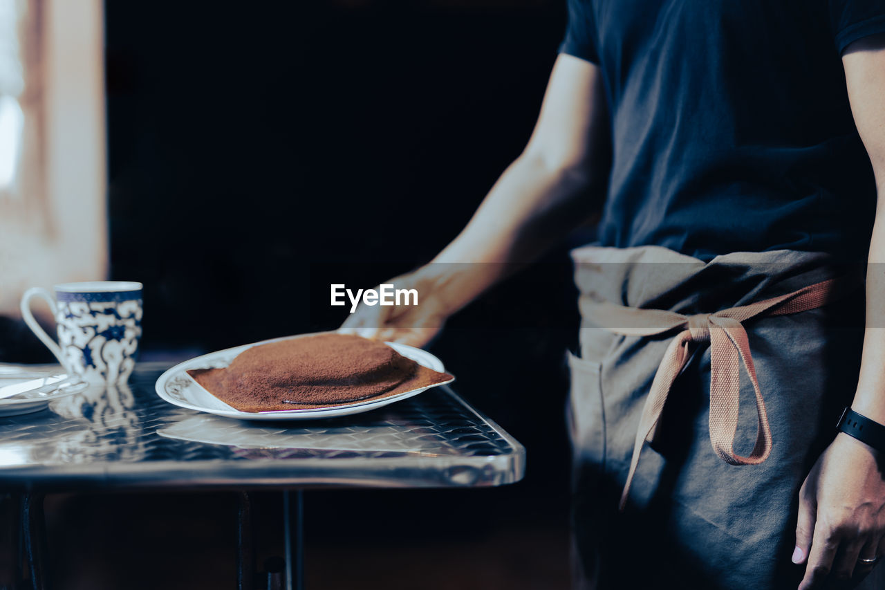 Midsection of man holding chocolate cake on table