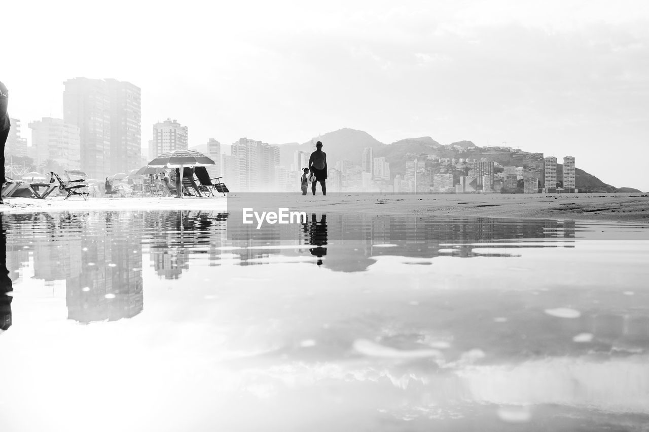 reflection, water, building exterior, architecture, real people, built structure, outdoors, sky, day, nature, one person, waterfront, leisure activity, city, modern, lifestyles, men, women, full length, beauty in nature, skyscraper, scenics, people