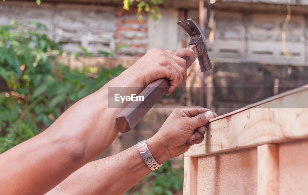 Close-Up Of Hand Hammering Nail