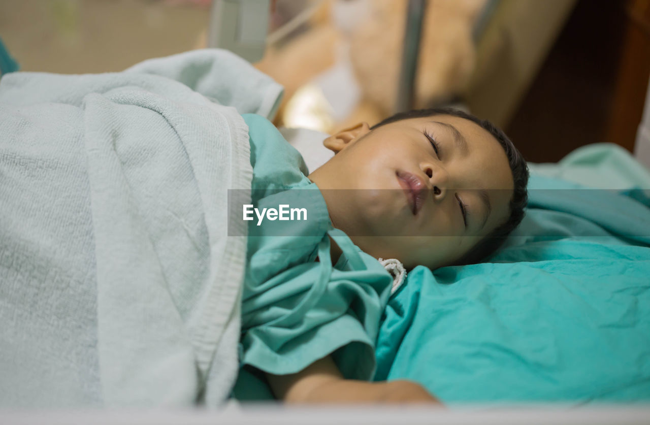 lying down, bed, eyes closed, child, relaxation, one person, sleeping, furniture, indoors, childhood, real people, resting, boys, males, innocence, selective focus, headshot, men, healthcare and medicine