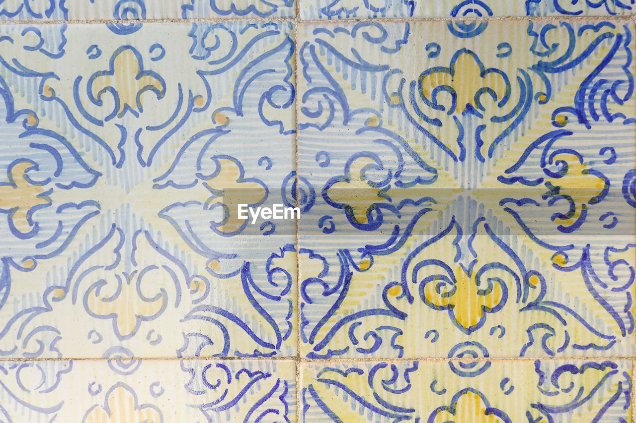 pattern, backgrounds, full frame, tile, indoors, no people, blue, design, flooring, wall - building feature, close-up, multi colored, yellow, floral pattern, repetition, built structure, abstract, creativity, architecture, text, tiled floor