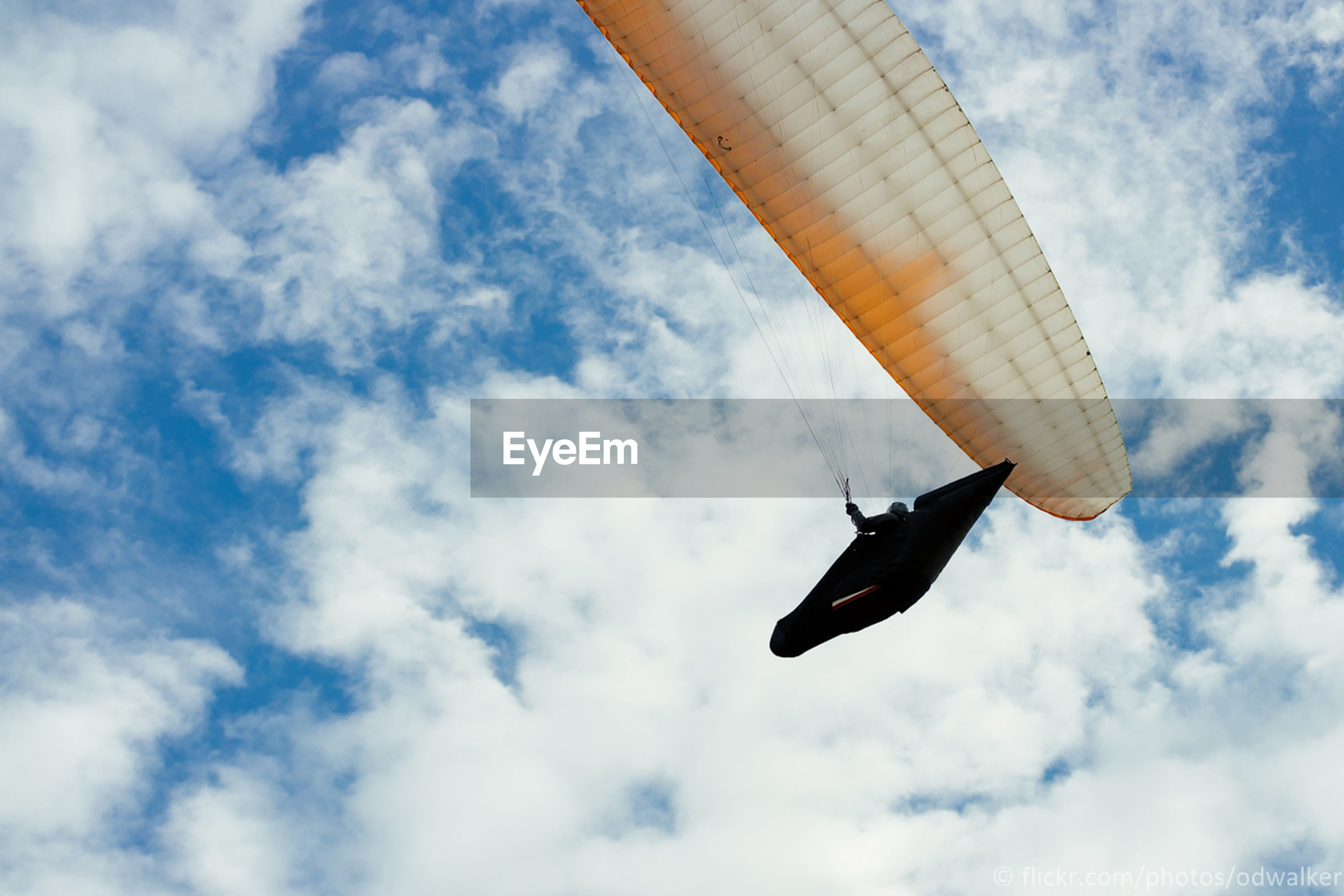 low angle view, sky, flying, adventure, cloud - sky, freedom, extreme sports, mid-air, real people, day, parachute, transportation, one person, outdoors, paragliding, nature