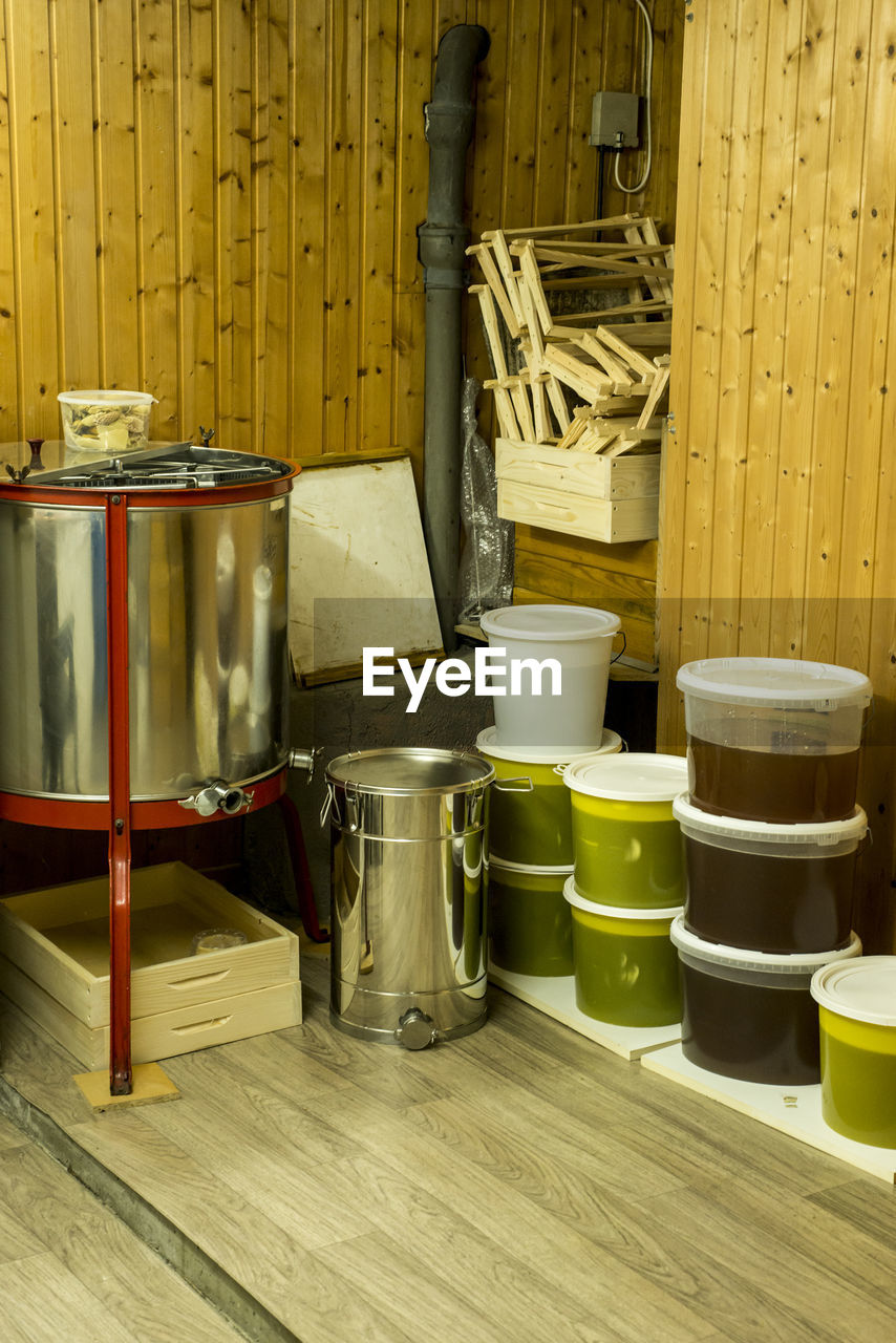 container, wood - material, indoors, no people, drum - container, still life, food and drink, metal, domestic room, table, drum - percussion instrument, yellow, large group of objects, kitchen utensil, household equipment, food, group, day, musical instrument, group of objects, saucepan