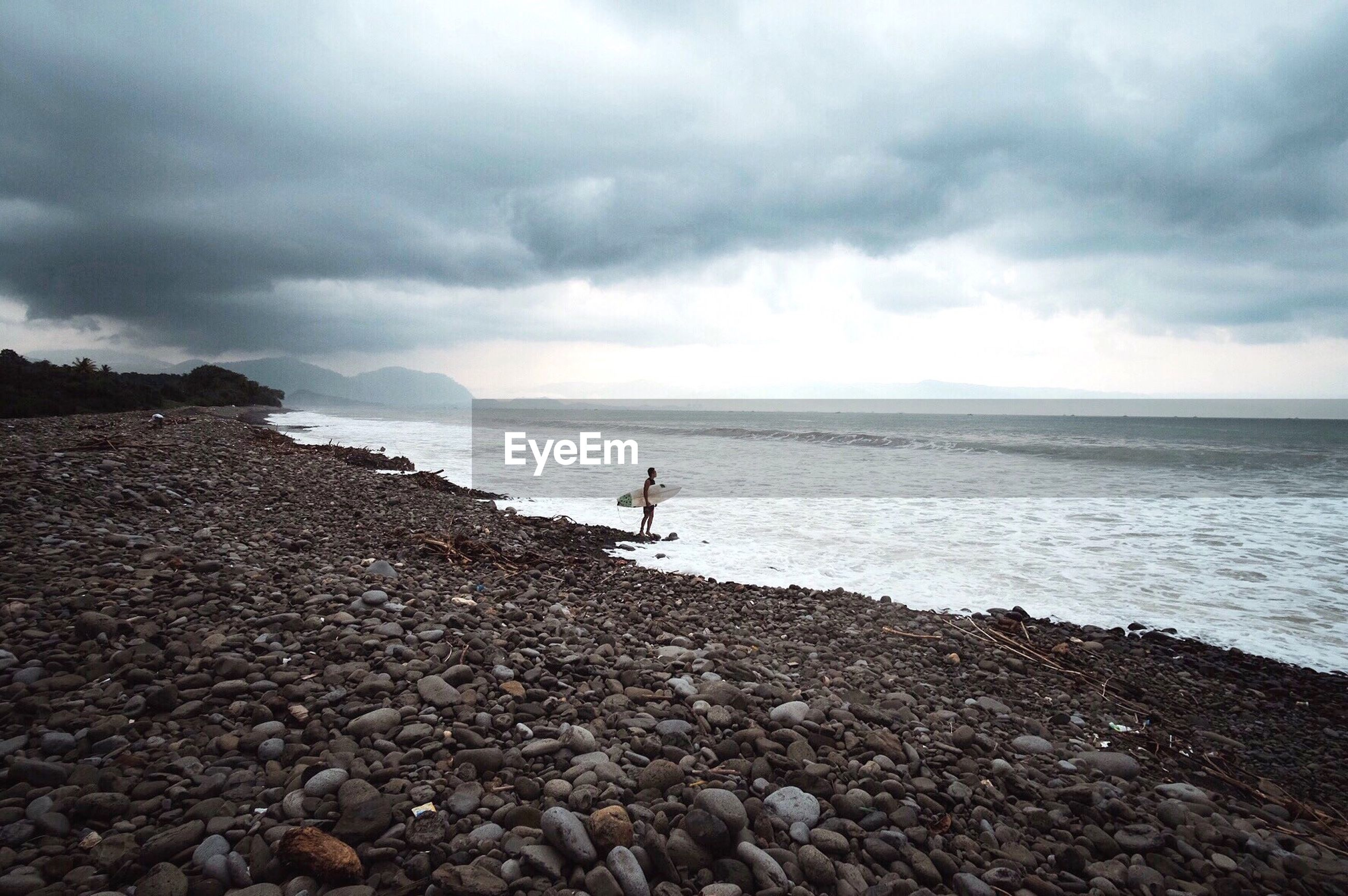 Man standing with surfboard at shore against cloudy sky