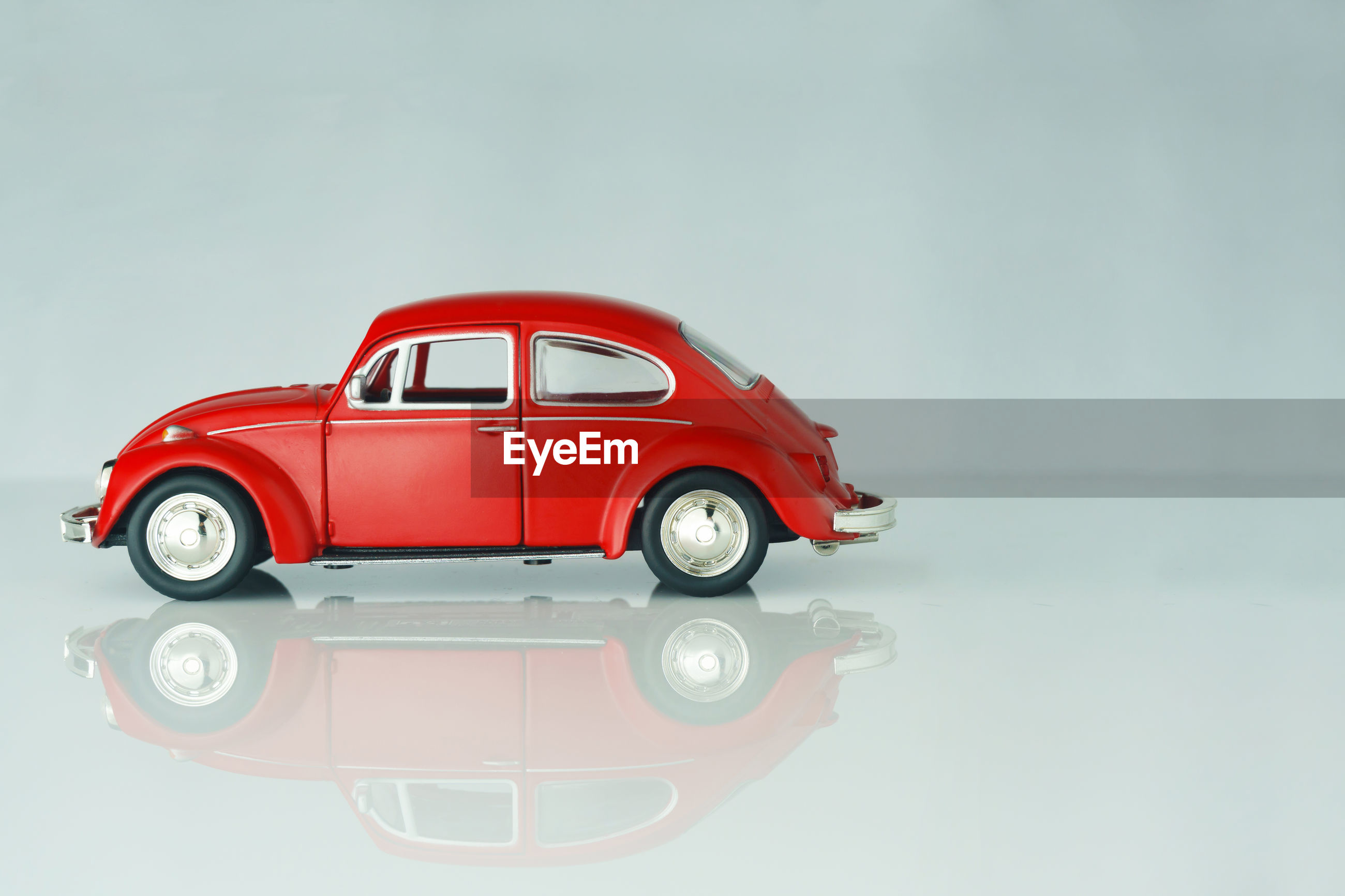 Red toy car against on glass table