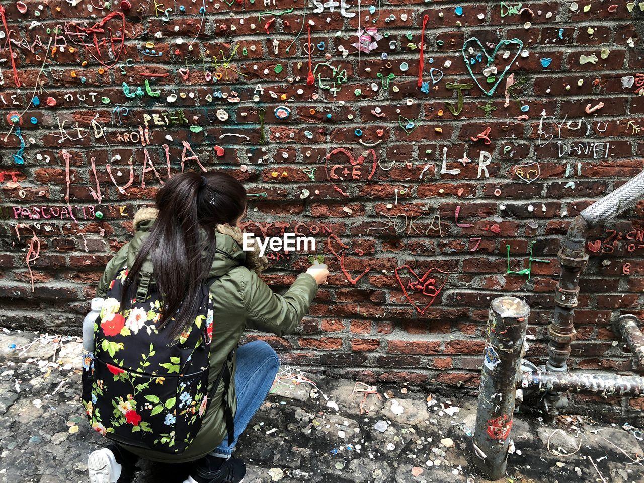 Woman decorating gum wall