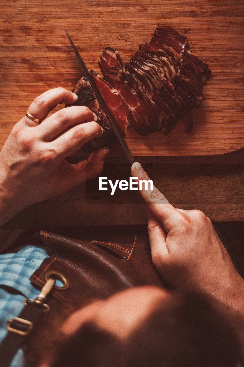 High angle view of hand holding charcuterie on table