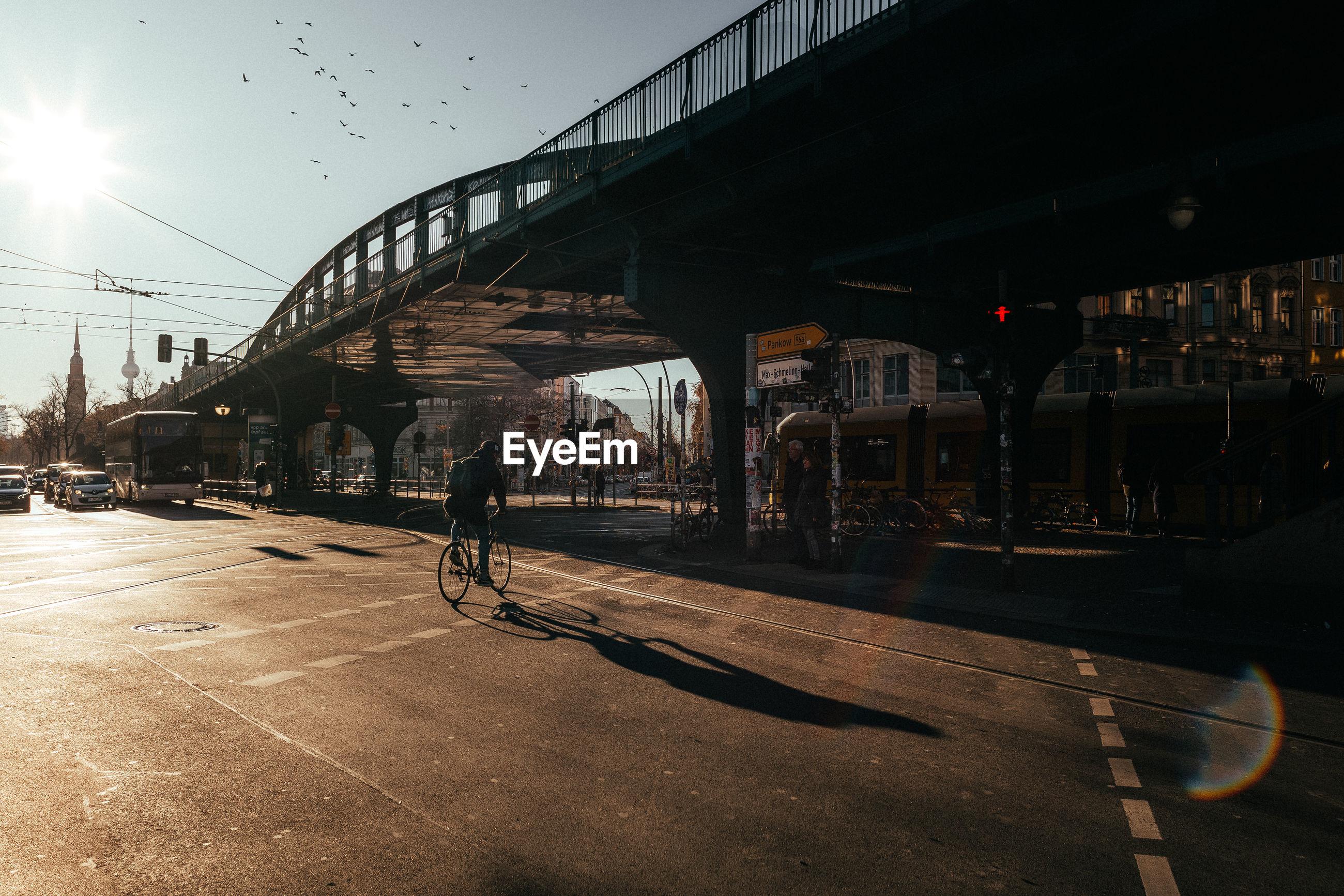 REAR VIEW OF MAN CYCLING ON BRIDGE