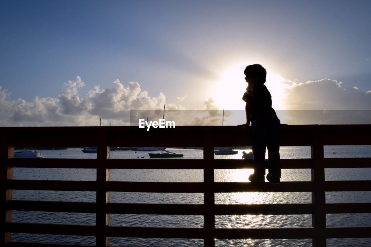 Full Length Of Child Standing On Railing By Sea Against Sky